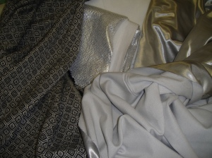 Materials for my winter coat (clockwise from left): fashion fabric, foil-backed underlining, plain underlining, Kasha lining right side, Kasha lining wrong side.